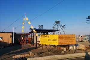 An area where a house once stood now welcomes visitors in Arahama. You can view pictures of the town before and during the tsunami. Yellow flags can be found in some areas which express the desires of those that want to return.