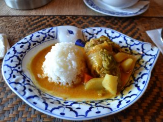 A tasty main dish of rolled cabbage, vegetables, and rice in a delicious curry sauce