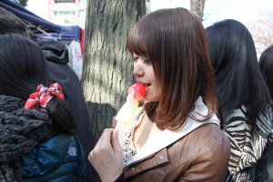 A girl eating penis candy