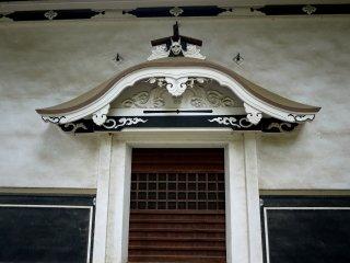 A grinning demon over the door
