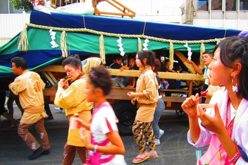 A lion-dance cart flanked by locals dressed in parade gear playing and singing accompanying music