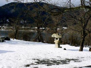 Une lanterne de pierre abimée sous la neige