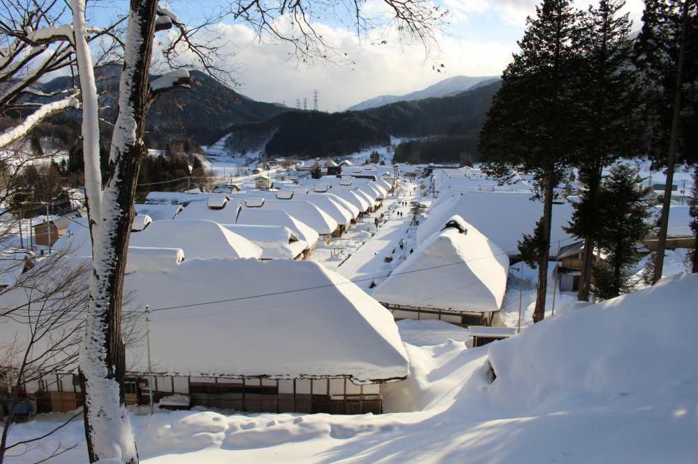 Rows of thatched buildings blanketed in snow
