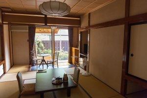 Une chambre japonaise de style traditionnel, avec un sol tapissé de tatami et un patio avec onsen et jardins privés