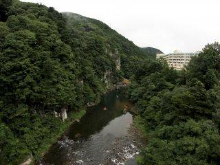 Cảnh vật nhìn từ cây cầu.Bạn có thể nhìn thấy khách sạn phía bên phải của ảnh và những người tham gia mạo hiểm chèo bè trên dòng sông phía dưới