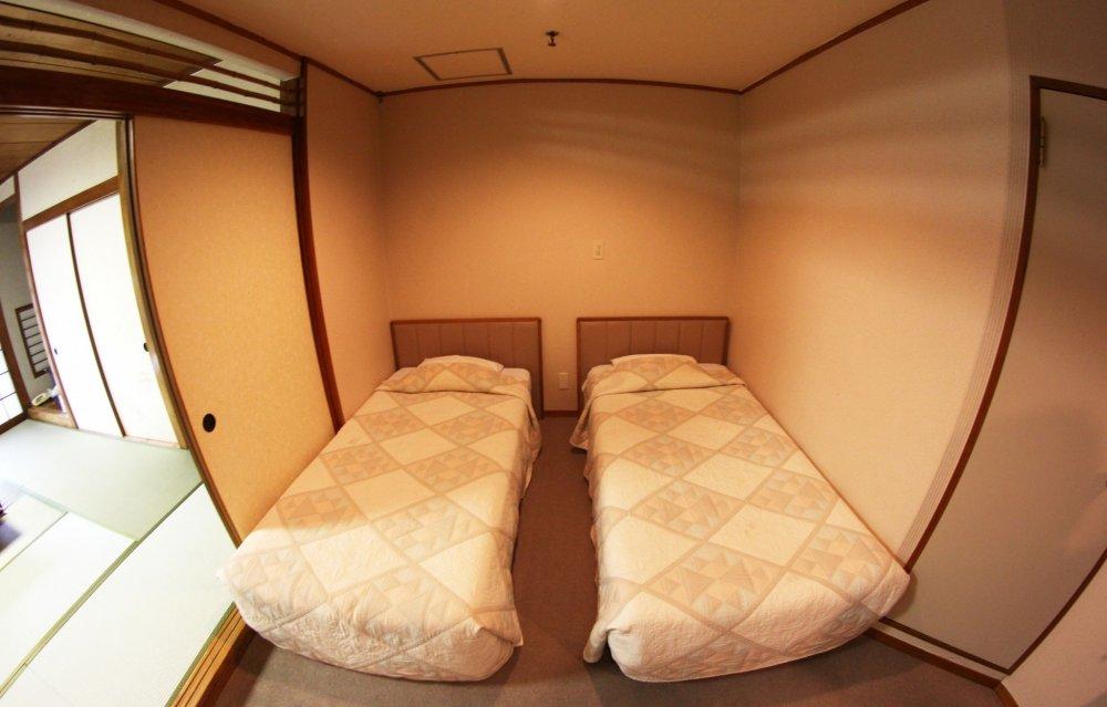 Phía khác của căn phòng là 2 chiếc giường theo phong cách phương tây, cũng như một chiếc bàn nhỏ, 2 chiếc ghế và một tủ lạnh nhỏ