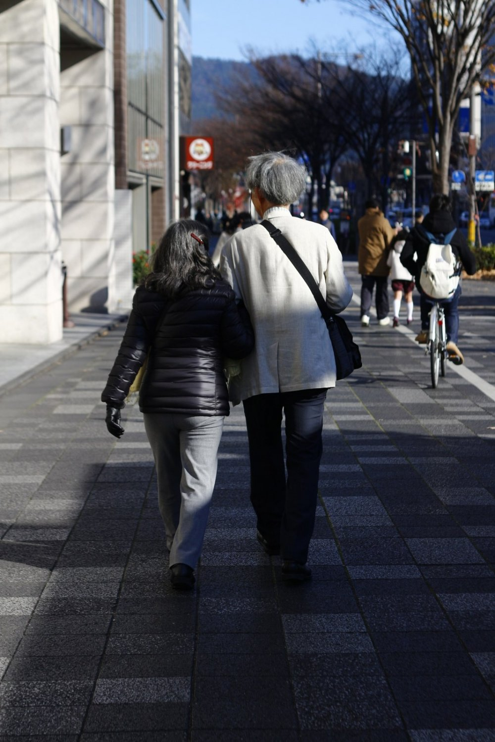 An old couple with a romantic vibe walking towards the Kyoto City Hall ...