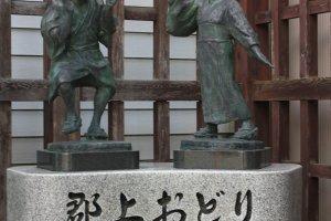 Une statue représentant deux personnes en train de danser au festival Gujo Odori