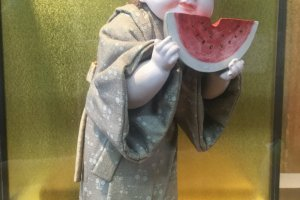 Delightful doll of a child eating a watermelon.