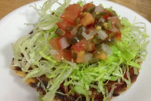 tostada with homemade salsa and refried beans