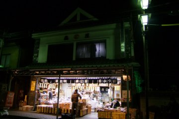 <p>A mom-and-pop shop lit up at night</p>