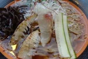 Taburannya berupa dua iris rebung bakar, irisan timun jepang, rumput laut, daun bawang, dan seiris tai sashimi (ikan mentah).