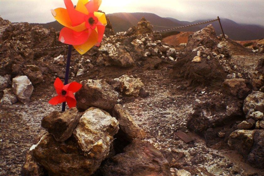 กังหันลมปักบนกองหินในบริเวณที่เรียกว่า นรก ว่ากันว่ากองหินเหล่านี้ วิญญาณเด็กๆ เป็นผู้ก่อเพื่อข้ามแม่น้ำซันโซ รอบๆ เป็นลานหินกว้าง ไม่มีพืชพรรณขึ้นเนื่องจากสภาพทางธรณีวิทยาที่เป็นภูเขาไฟมีชีวิต ทำให้พื้นดินบริเวณนั้นเป็นกรดมาก ควันขาวพุ่งจากบ่อโคลนเดือดเป็นระยะ ตามตำนานเล่าว่ามีบ่อโคลนทั้งหมด 108 บ่อ เท่ากับกิเลสตัณหาทางโลก 108 อย่างพอดี