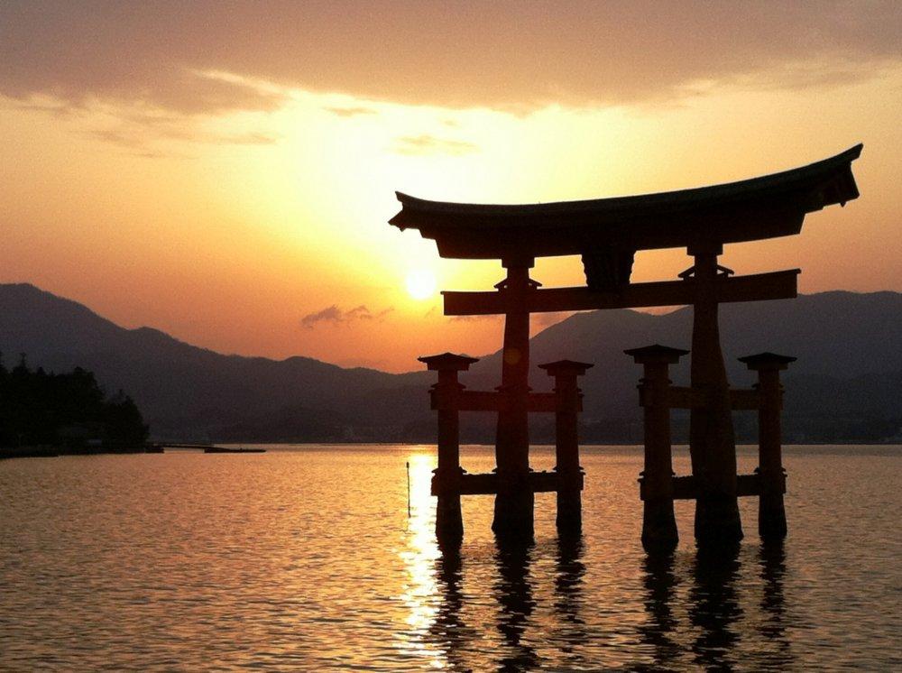 เสาโทริอิยักษ์ สัญลักษณ์ของศาลเจ้าอิซุคุชิม่าและเกาะมิยาจิม่าขณะพระอาทิตย์กำลังตกดิน