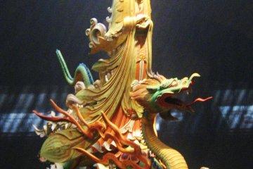 Kannon (Avalokitesvara) riding on a dragon. Wood and colour, 20th century