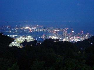 """Khung cảnh ban đêm của nhà kính và thành phố cảng Kobe bên dưới, phát sáng trong """"khung cảnh triệu đô la"""" của Kobe."""