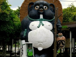 Giant tanuki and public phone outside the JR station