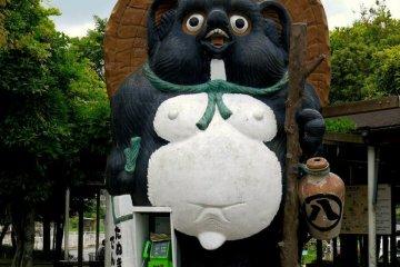 <p>Giant tanuki and public phone outside the JR station</p>