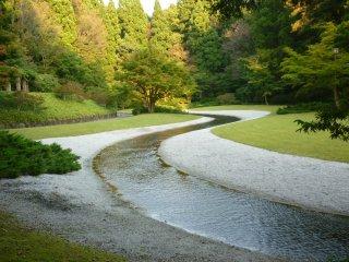 코이 연못에 물을 공급하는 시냇물이 공원을 가로질러 흐르고 공원 배치의 예술적인 디자인을 보여준다.