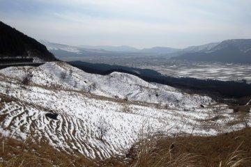 <p>ท้องทุ่งที่ถูกหิมะปกคลุมตามเส้นทางระหว่าง Kuju และเทือกเขา Aso</p>