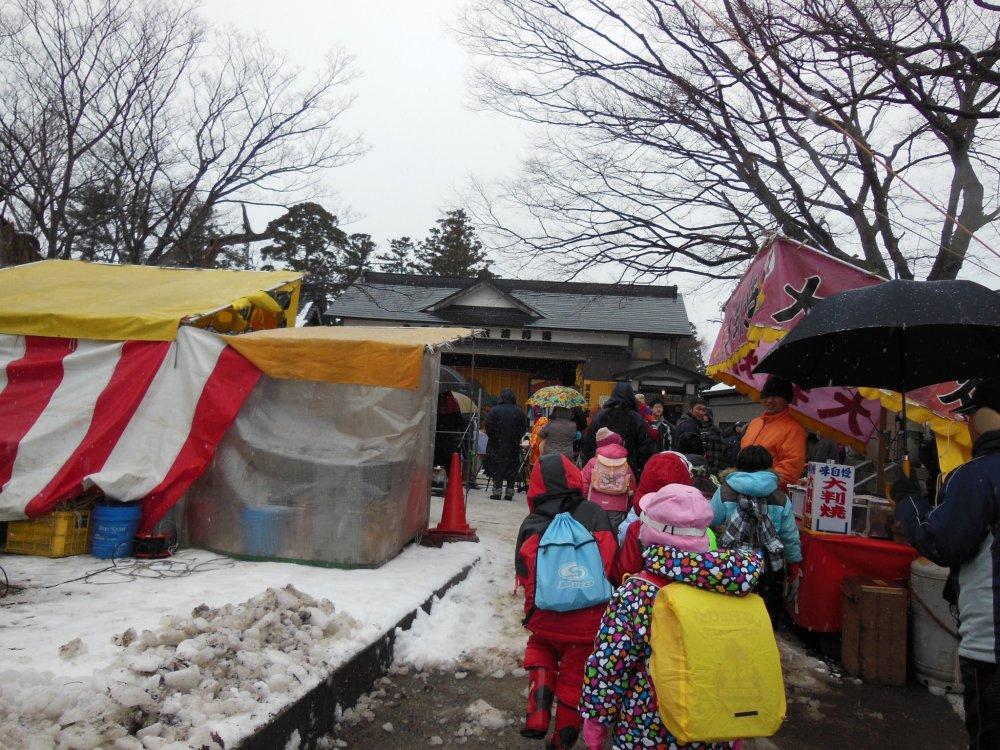 Children, parents, visitors, and residents pour into the shrine grounds to see the performance.