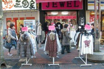 <p>The melting pot: rails of bargains outside a clothes store next to a ramen shop.</p>