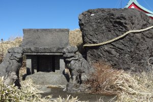 Just before the red shrine gate, there is a rock with a sacred straw rope