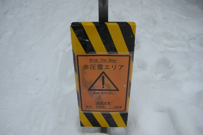 DROP THE BEAR! This is the only sign at the top of the mountain. The Japanese warns this is an uncompacted snow area, so it will be challenging--even without bears.