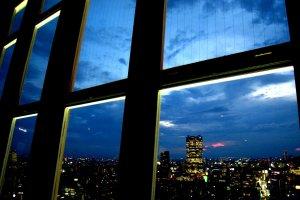 แสงสีของเมืองโตเกียวยามค่ำคืนที่มองผ่านกระจกบานใหญ่ในมุมหนึ่งบนชั้น Mani Observatory ของหอคอยโตเกียว (Tokyo Tower) ที่ระดับความสูง 150 เมตร