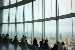 ชิลล์ชมกรุง : ที่ชั้น 52 ของ Tokyo City View นั้น เป็นจุดชมวิวผ่านกระจกใสบานใหญ่ ซึ่งนี่คืออีกหนึ่งมุมยอดนิยมที่เราสามารถนั่งชมหอคอยโตเกียวพร้อมวิวสวยในมุมสูงได้อย่างสบายๆ ไม่มีมีเบื่อ
