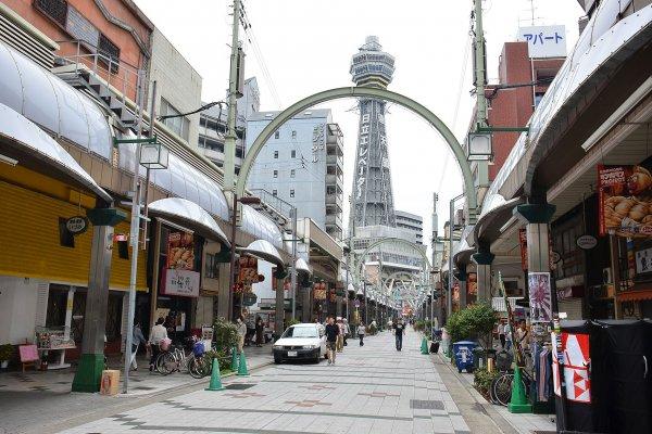 ทางเดินที่มุ่งสู่หอคอย Tsutenkaku เต็มไปด้วยร้านรวงต่างๆ ที่เต็มไปด้วยเอกลักษณ์ของย่านเก่าแก่แห่งนี้