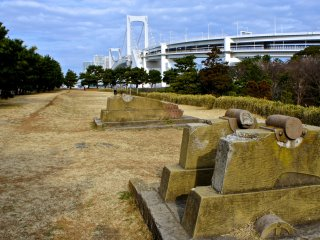 The canon ruins at The Third Daiba, or Daiba Park, with the majestic Rainbow Bridge in the background