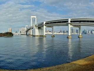 Backside of The Third Daiba, a panoramic view of the Rainbow Bridge and the city of Tokyo in the background. You can also see Tokyo Tower between the two large columns of the bridge.