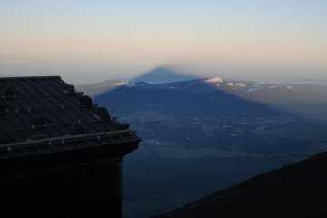 This is called Kage-Fuji, meaning Shadow of Mt.Fuji. This is a phenomenon where you see a shadow of Mr.Fuji appearing on the sea of clouds at the sunrise or the sunset.