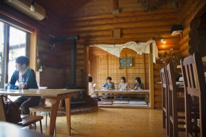 The log cabin even contains a tatami mat room next to the main dining area; note the wood-burning stove behind the table on the left