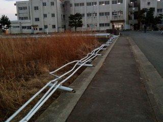 Chegando à Escola de Yuriage. O separador de aço está dobrado num ângulo impossível devido à força da água cheia de destroços.
