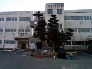 Um pequeno monumento em frente à escola serve de local para rezar e refletir. Enquanto isso, o relógio no exterior do edifício não se moveu desde as 2:46PM de 11 de Março de 2011, a hora a que o terramoto atacou.