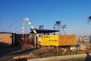 Uma área onde um dia esteve uma casa, agora dá as boas-vindas aos visitantes de Arahama. Pode ver fotografias da cidade antes e durante o tsunami. Bandeiras amarelas podem ser encontradas em alguns sítios, exprimindo os desejos daqueles que querem regressar.