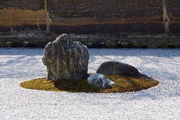 <p>A group of rocks on the moss-coated island</p>