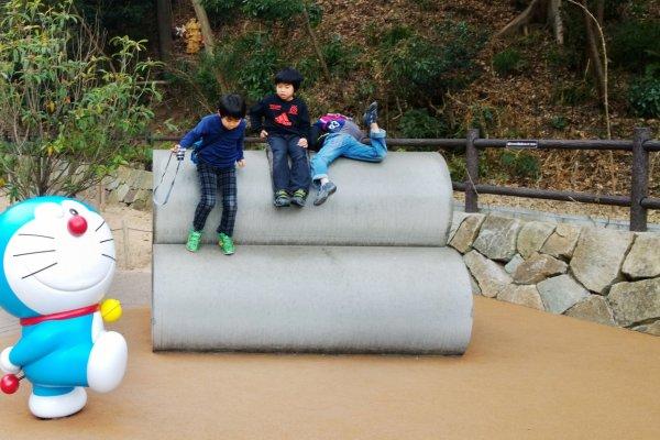 นี่ล่ะ! มุมขวัญใจมหาชน > ไม่ว่าจะวัยไหนก็อยากซนในมุมนี้กันทั้งนั้น เช่นเดียวกับแก๊งค์ 3 หนุ่มน้อยชาวญี่ปุ่นนี้ที่กำลังปีนป่ายท่อน้ำกันอย่างสนุกสนาน สำหรับมุมป๊อบปูล่าห์มหาชนนี้ตั้งอยู่บนชั้นดาดฟ้าของพิพิธภัณฑ์ Fujiko F. Fujio ซึ่งแน่นอนว่านี่คือฉากสัญลักษณ์ที่ทุกคนจดจำกันได้แม่นยำว่ามาจากการ์ตูนเรื่องโดราเอม่อนนั่นเอง