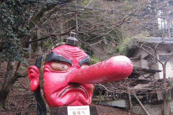 รูปปั้นเทพเจ้าTenguสีแดงสดน่าเกรงขาม ตั้งอยู่หน้าสถานีรถไฟKurama