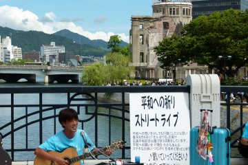 <p>Museum playing on the bridge with view of A-bomb dome behind</p>