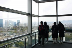 แลปราสาท > กลุ่มเด็กนักเรียนมัธยมปลายของญี่ปุ่นกำลังยืนดูปราสาทโอซาก้าและเมืองอันรุ่งเรืองในยุคปัจจุบันโดยรอบ ซึ่งบริเวณนี้คือกระจกใสตรงโถงบันไดเชื่อมชั้นที่เป็นหนึ่งในจุดชมวิวเมืองโอซาก้าอันแสนพิเศษและสวยงามไม่เหมือนใคร