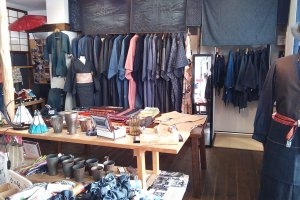 Denim kimonos that are original to the shop hanging on the rack; accessories on the table.