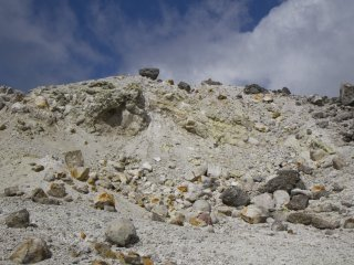The barren peak of Mt. Io, littered with sulfur
