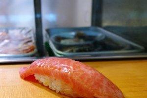 นี่แหละซูชิหน้าปลาโอโทโร่ (Otoro) หรือปลาทูน่า ซึ่งเป็นเมนูพระเอกของทางร้านที่ใครๆ ก็อยากมาลิ้มลอง โดยปลาทูน่าที่สดใหม่ทุกวันนั้นจะถูกแร่เนื้อบางๆ ให้เห็นการแทรกตัวของไขมันที่กำลังพอเหมาะ โปะลงบนข้าวปั้นในสูตรเฉพาะตัวที่ทำให้ความอร่อยนั้นเหมือนเนื้อปลากำลังละลายในปาก เป็นความอร่อยราวขึ้นสวรรค์เลยทีเดียว