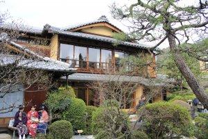 บ้านสองชั้นที่มีประตูเป็นกระจกทั้งหมด ทำให้คุณมองเห็นความสวยงามของการจัดสวนแบบญี่ปุ่น มีสาวๆในชุดกิโมโนมานั่งรอคิว