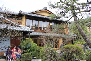 <p>A 2 story Japanese house with glass doors, which allow you to admire the beauty of a Japanese garden. The girls in kimono are waiting to get in.</p>