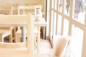 บรรยากาศสุขๆ สบายๆ ภายในร้าน (สาขาเท็นโนจิ / โอซาก้า) กับเก้าอี้ไม้ในห้องกระจกโปร่งชวนชิลล์