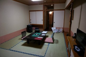 <p>ภายในห้องพักก่อนที่พนักงานจะมาปูที่นอนให้ จะมีโต๊ะและเก้าอี้นั่งแบบญี่ปุ่นตั้งอยู่กลางห้องให้นั่งพักผ่อน</p>